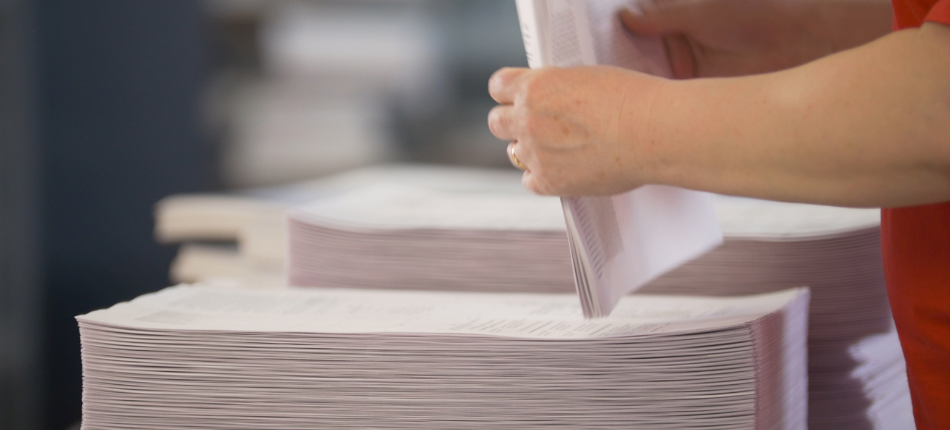 Close up of an employee collating a stack of papers after using a production printer.