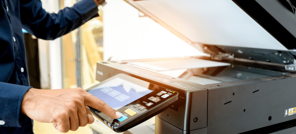 Close up of a man clicking a button on an office copier to signify a copier lease.